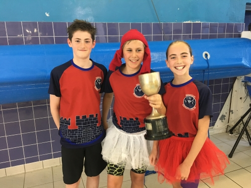 Windsor swimmers in festive attire, collect the Champions League Cup for the third consecutive Year.